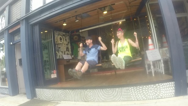 Dennis and Kimberly Goza on swings in a storefront.