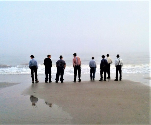 8 men well-dressed in hats, long sleeve shirts and suspenders admiring the ocean